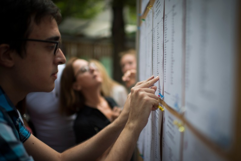 Des étudiants cherchent leurs noms sur le tableau des résultats du BAC d'un lycée