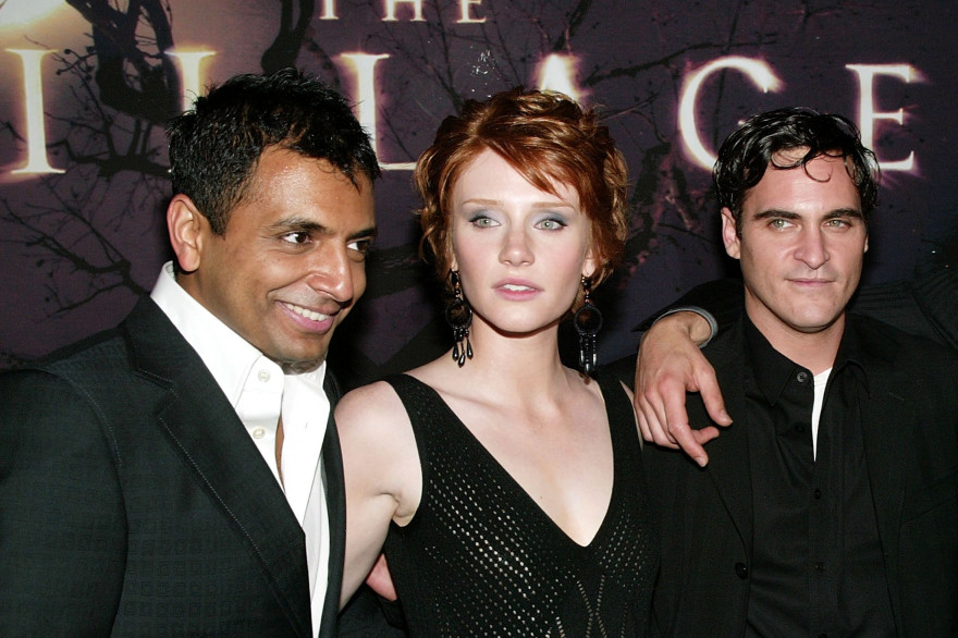 "M. Night Shyamalan avec Bryce Dallas Howard et Joaquin Phoenix au moment de la sortie de ""Le Village"" (2004)"