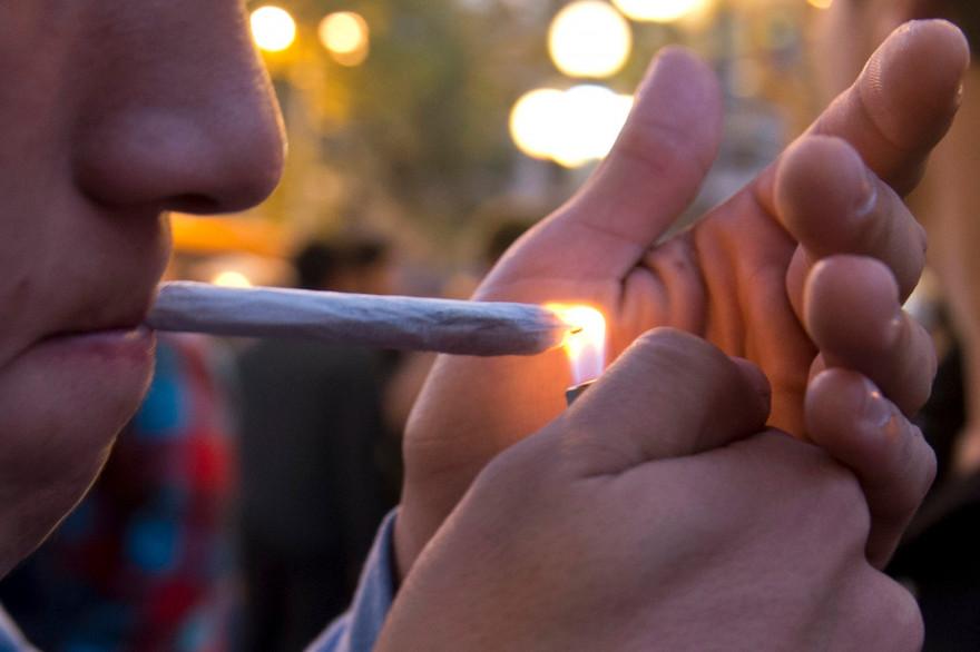 """Un jeune homme allume un """"joint"""" de cannabis (illustration)"""