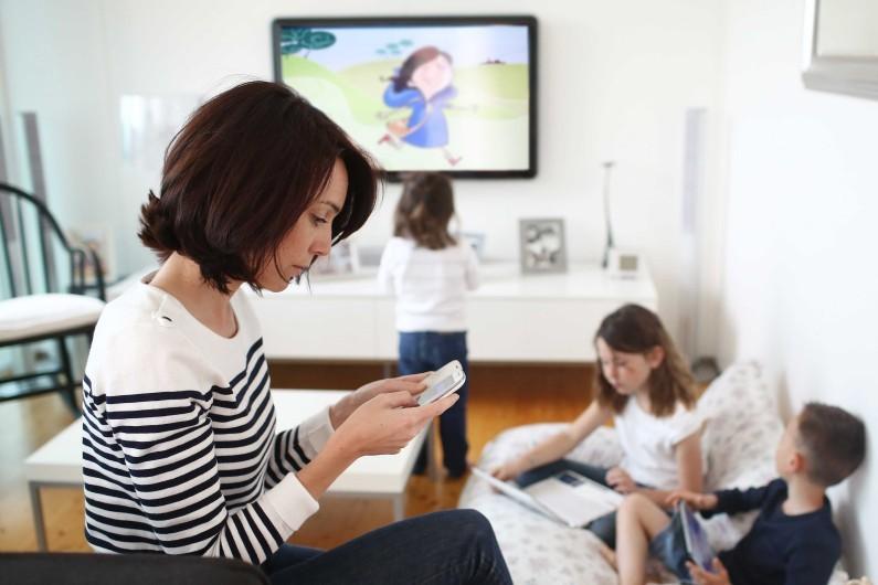 Une mère et ses enfants devant plusieurs écrans (illustration)