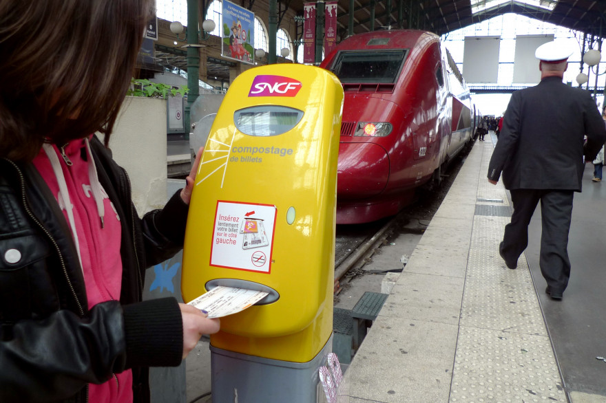 Une utilisatrice composte son billet SNCF dans une gare (illustration)