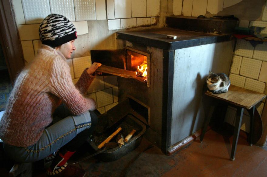 Une femme allume un chauffage à bois (photo d'illustration).