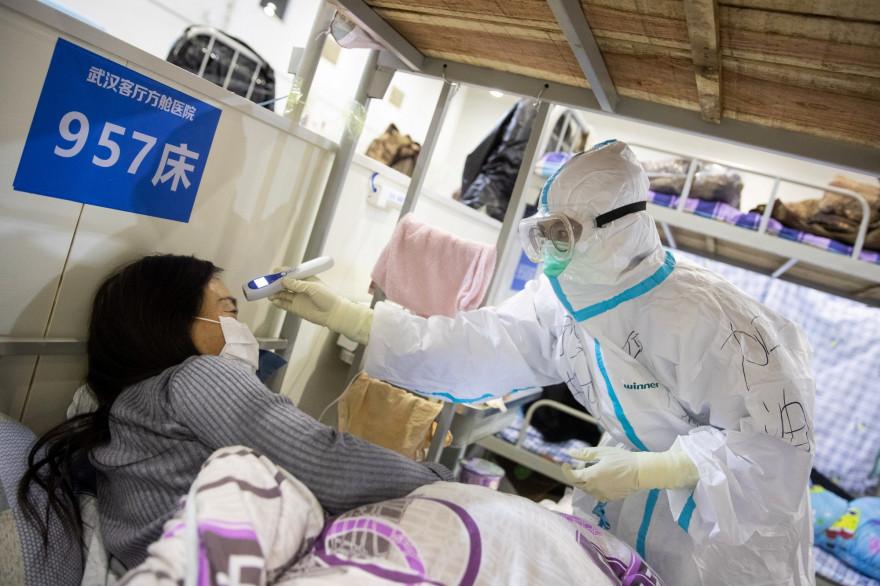 Une membre de l'équipe médicale d'un hôpital de Wuhan prend la température d'une patiente.