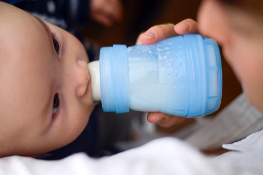 Un bébé boit son biberon de lait (illustration)
