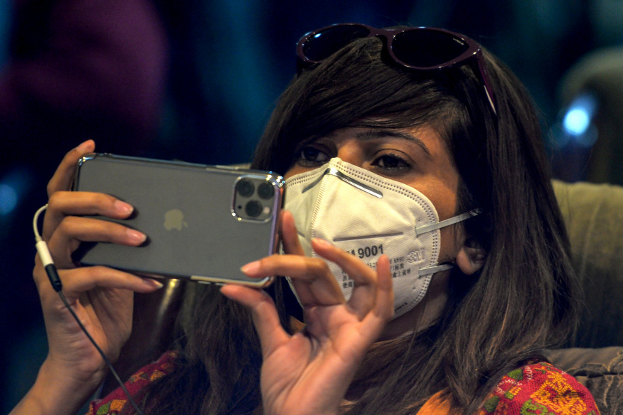 Une journaliste pakistanaise le visage recouvert d'un masque de protection sur son smartphone le 10 mars 2020
