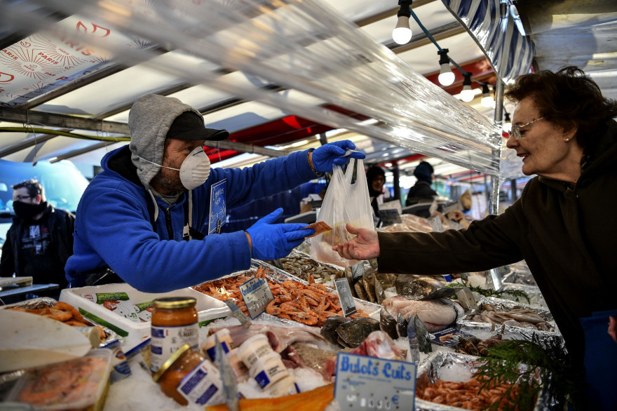 Un poissonier et une cliente sur un marché à Paris le 19 mars 2020.