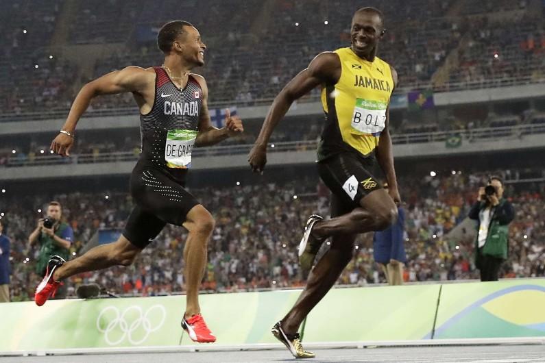Usain Bolt et Andre De Grasse s'échangent des sourires lors de la demi-finale du 200m à Rio.