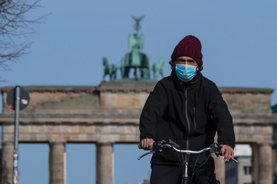 Un homme portant un masque fait du vélo devant la porte de Brandebourg, à Berlin, en Allemagne