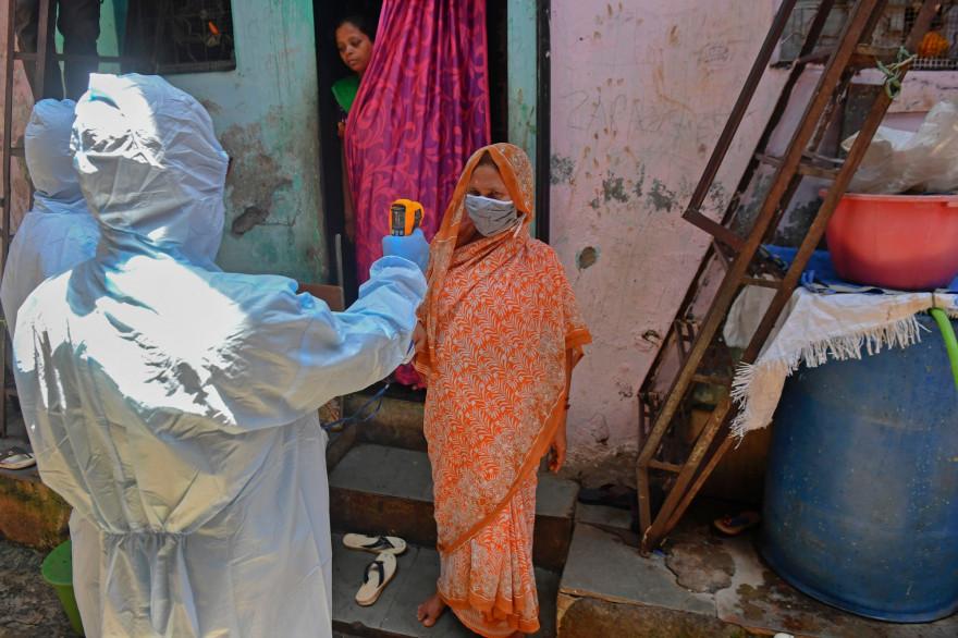 Un médecin prend la température d'une femme à Bombay en Inde, le 24 juin 2020