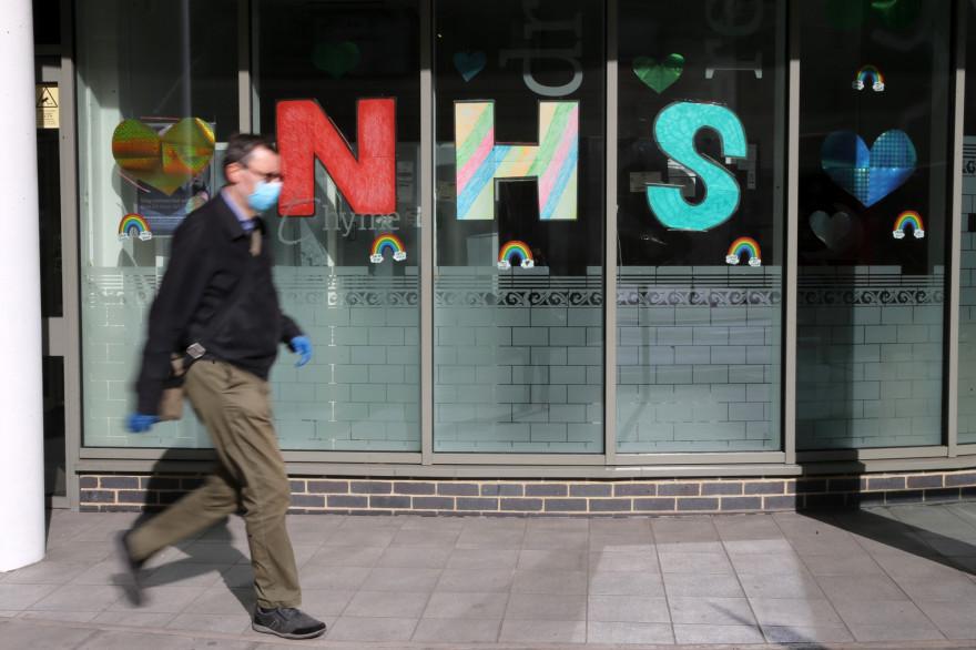 Un homme portant un masque contre le coronavirus, devant le NHS (National Health Service) à Londres, le 11 mai 2020.