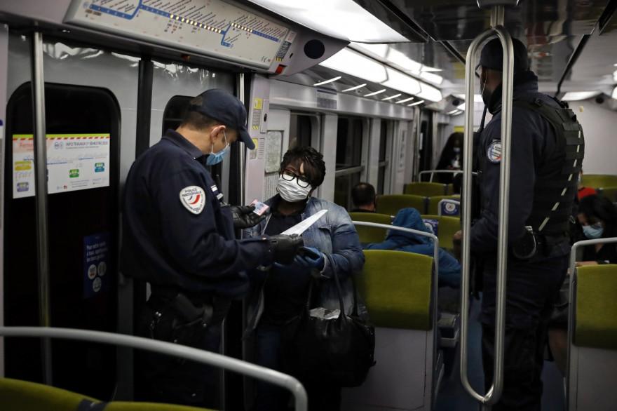 Des policiers procédant à un contrôle des attestations de déplacement et du port du masque, dans le métro, à Paris. (Illustration)