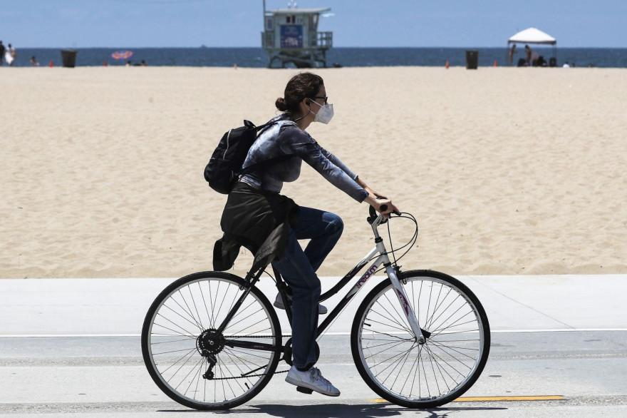 Une femme à vélo portant un masque