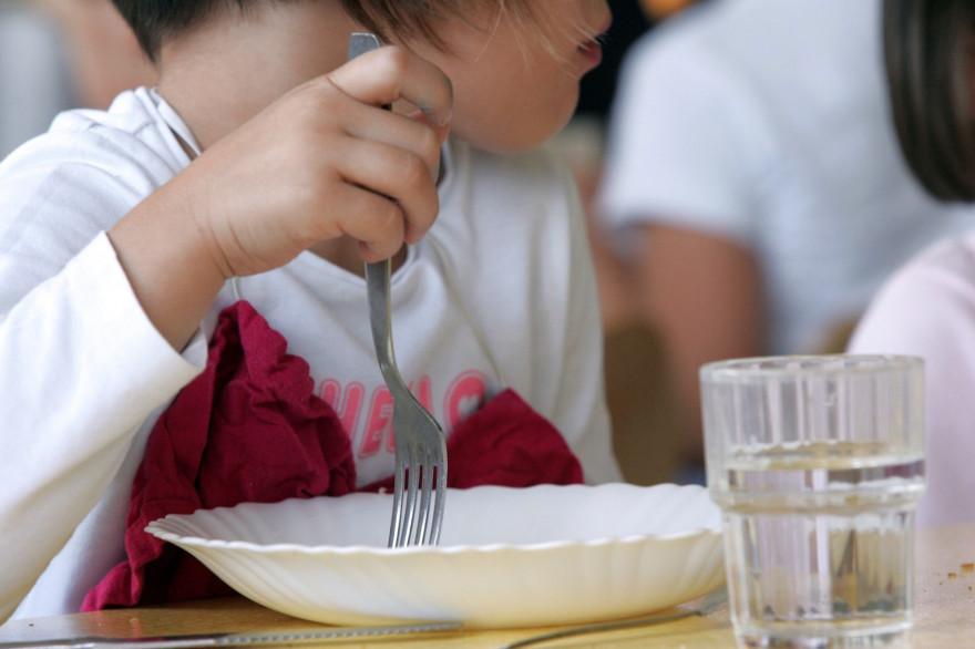 Une élève mange à la cantine (illustration)