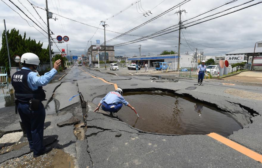 La police japonaise constate l'effondrement d'une route suite à un séisme à Tanatsuki.
