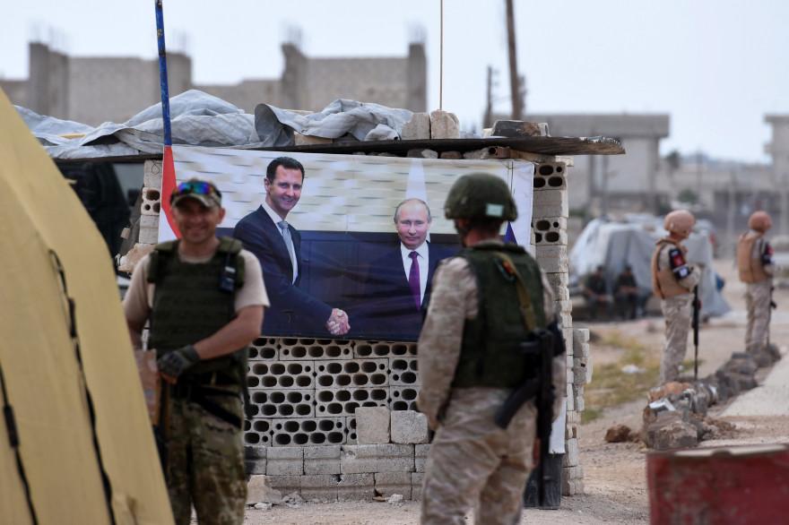 Des militaires russes devant une photo officielle des dirigeants syrien et russe, Bachar al-Assad et Vladimir Poutine
