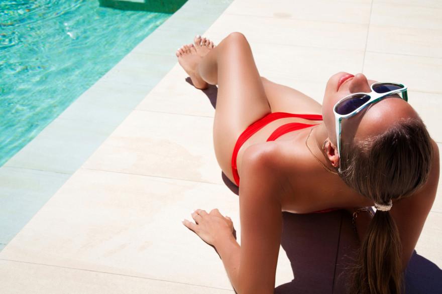 Une jeune femme en train de parfaire son bronzage au bord de la piscine (illustration)