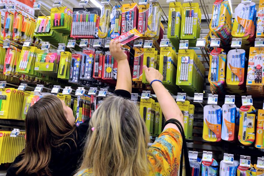 Une mère et sa fille achètent des fournitures scolaires dans un supermarché (illustration)