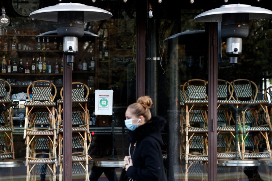 Une femme portant un masque, devant un restaurant fermé pendant le confinement.