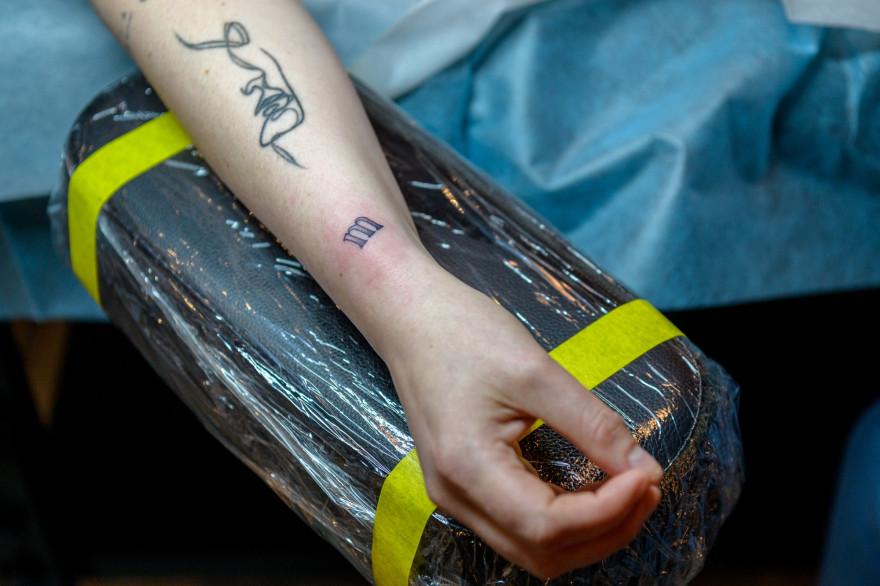 Abigail Glasgow montre ses tatouages temporaires à la boutique de tatouage éphémère le 21 avril 2021 à New York.