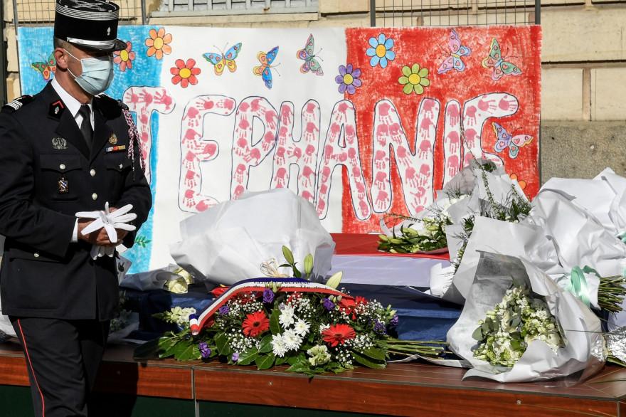 Un policier rend hommage devant des fleurs déposées en hommage à Stéphanie Monferme, une policière locale tuée, lors d'un rassemblement commémoratif le 26 avril 2021 à la mairie de Rambouillet.