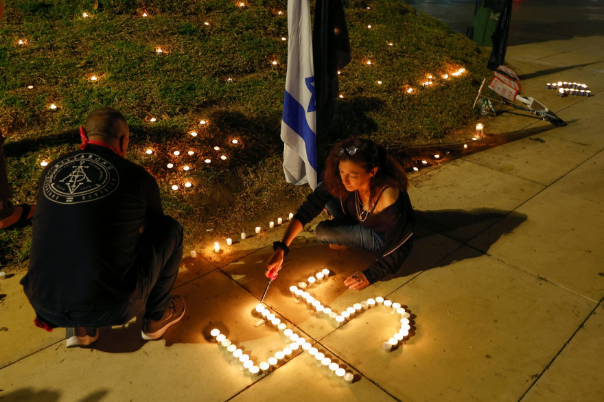 Des bougies scintillent près d'un drapeau israélien lors d'une veillée sur la place Habima, dans la ville côtière de Tel Aviv, le 1er mai 2021, au lendemain d'une bousculade meurtrière dans une ville de pèlerinage juive du nord du pays.